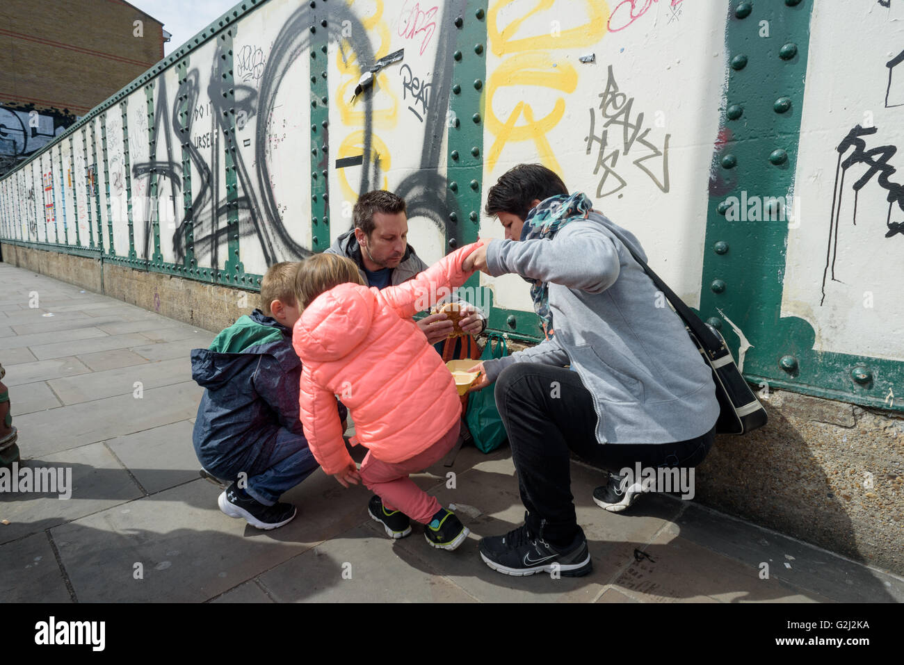 Family of four eating and sharing a beefburger crouched on the pavement of Brick Lane in London during the 1st of - Stock Image