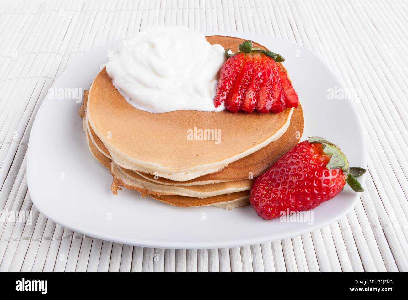 Pancakes on white plate and  background wiyh cream and strawberry - Stock Image