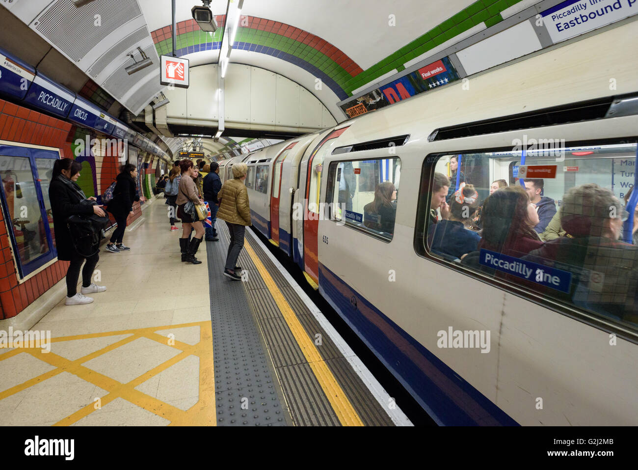 People preparing to board the London Underground Tube Train at Piccadilly Circus London - Stock Image