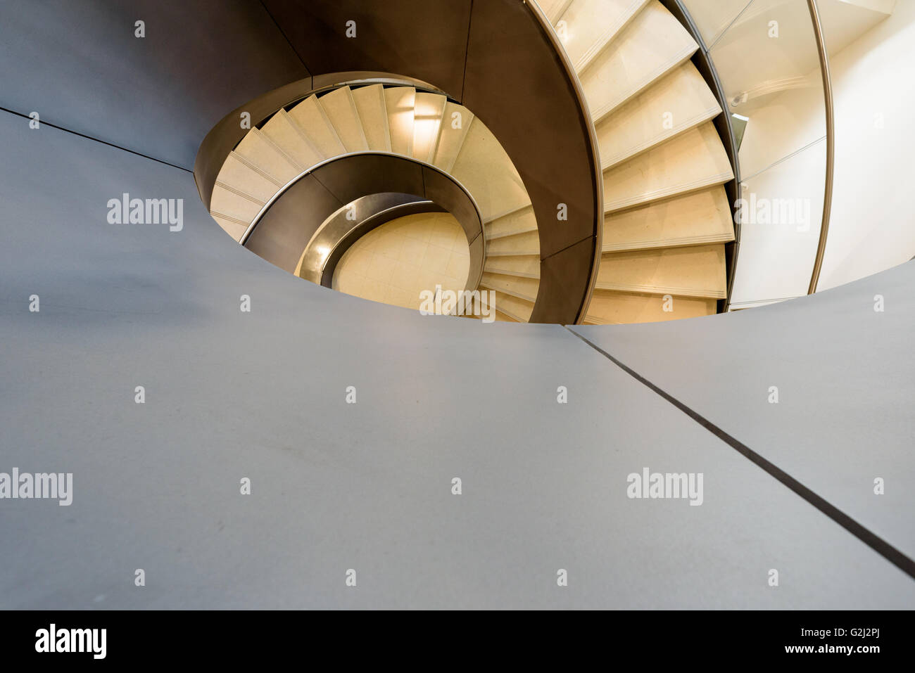 Modern spiral staircase in London at the Wellcome Collection museum at 183 Euston Rd, Kings Cross, London NW1 2BE - Stock Image