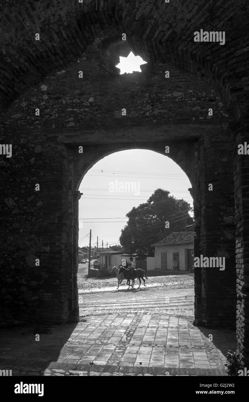 Santa Ana ruins framing two horse riders passing by. - Stock Image