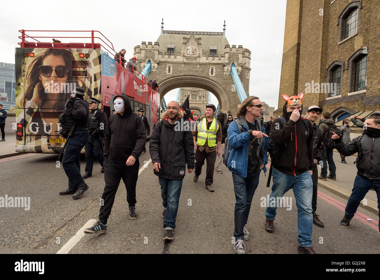 May Day Anarchist group with hidden faces, slogans and red flags walking across Tower Bridge May 1st 2016 Stock Photo