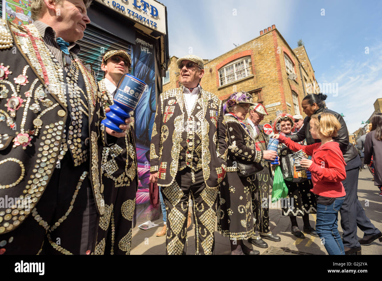 Traditional Pearly Kings and Queens in full costume collecting donations in London on Brick Lane Shoreditch - Stock Image