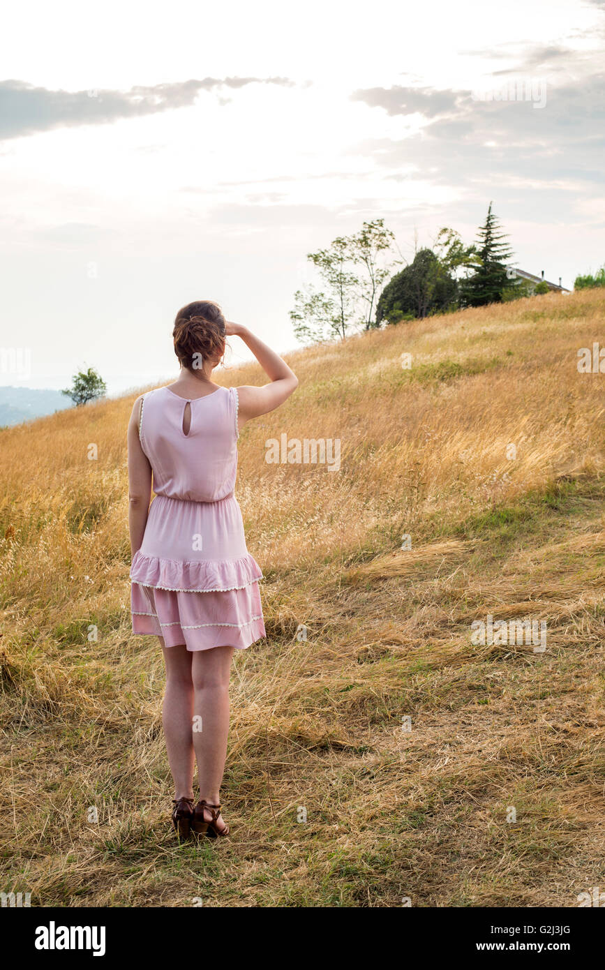 Woman in Pink Dress looking off into Distance in Field, Rear View - Stock Image