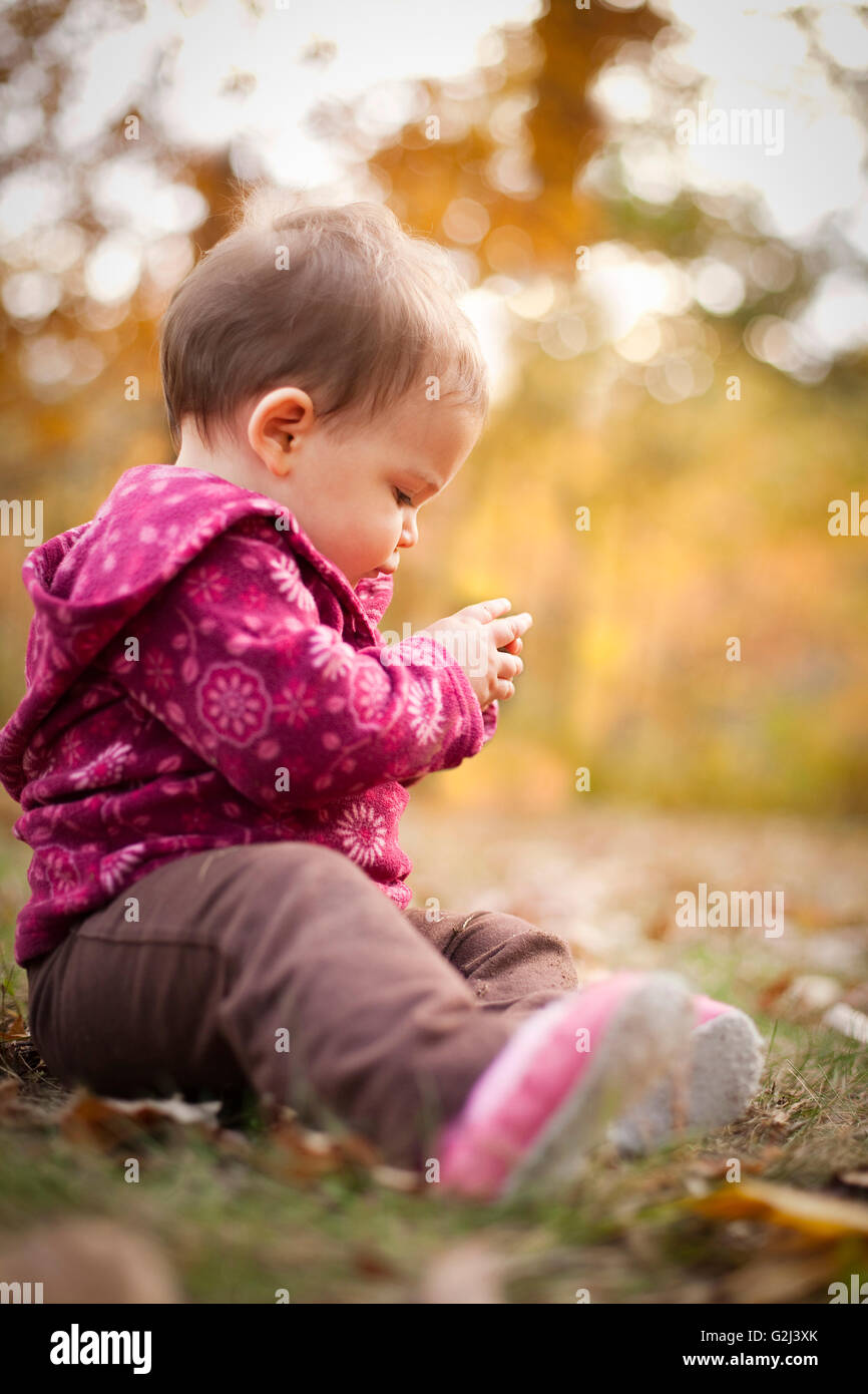 Young Child Sitting on Ground and Holding Acorn, Stratford, Connecticut, USA Stock Photo