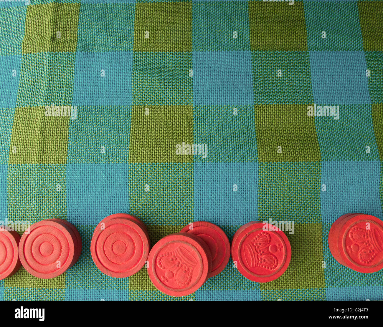 Red Wooden Checkers on Plaid Tablecloth Stock Photo