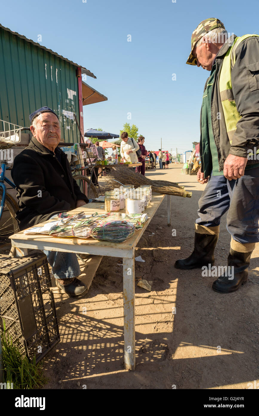 Aged elderly man from Tashkent sells home produced vegetable seeds for sale at a local farmers market in Russia - Stock Image