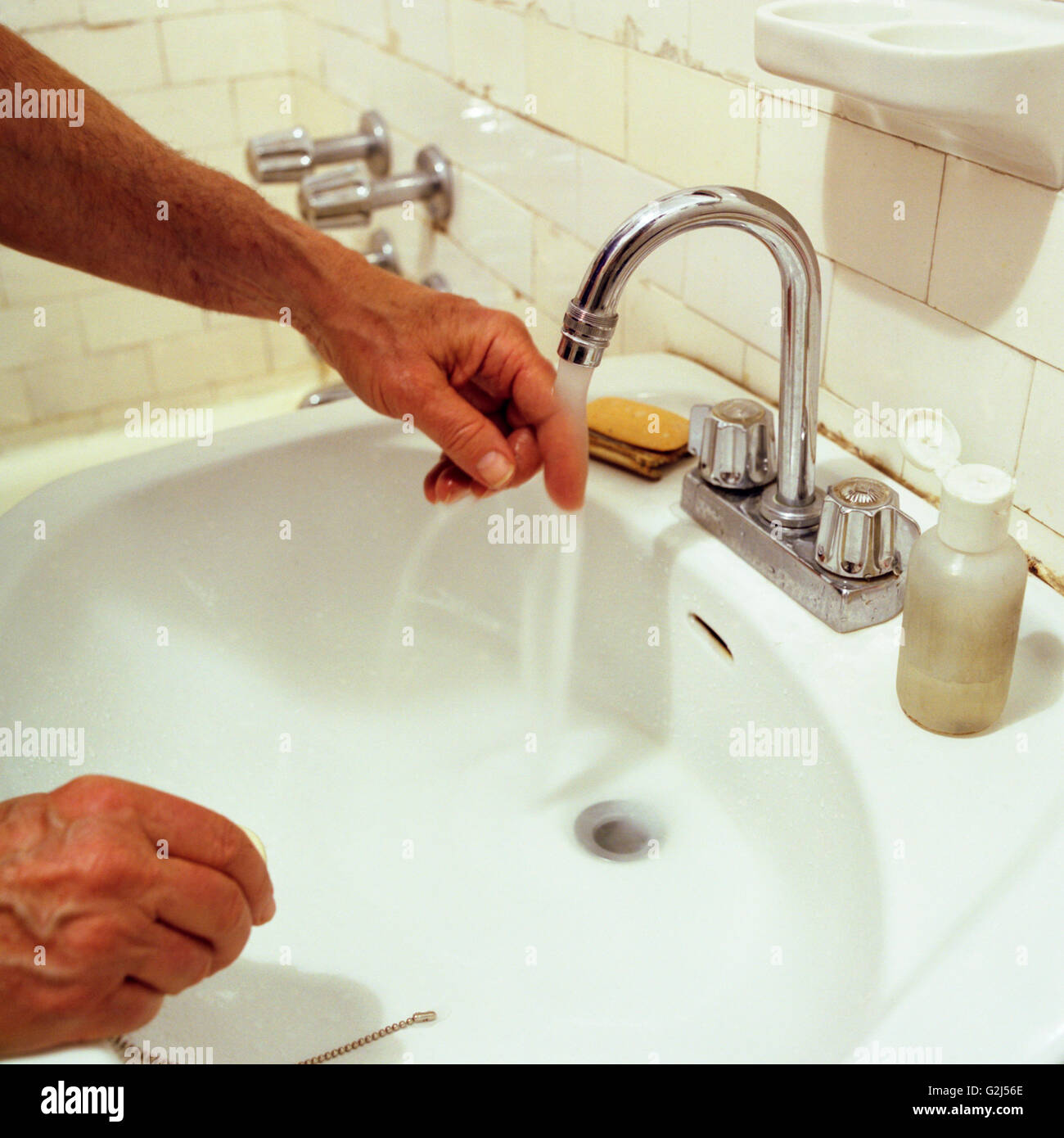 Elderly Man Testing Water Temperature From Sink Stock Photo Alamy