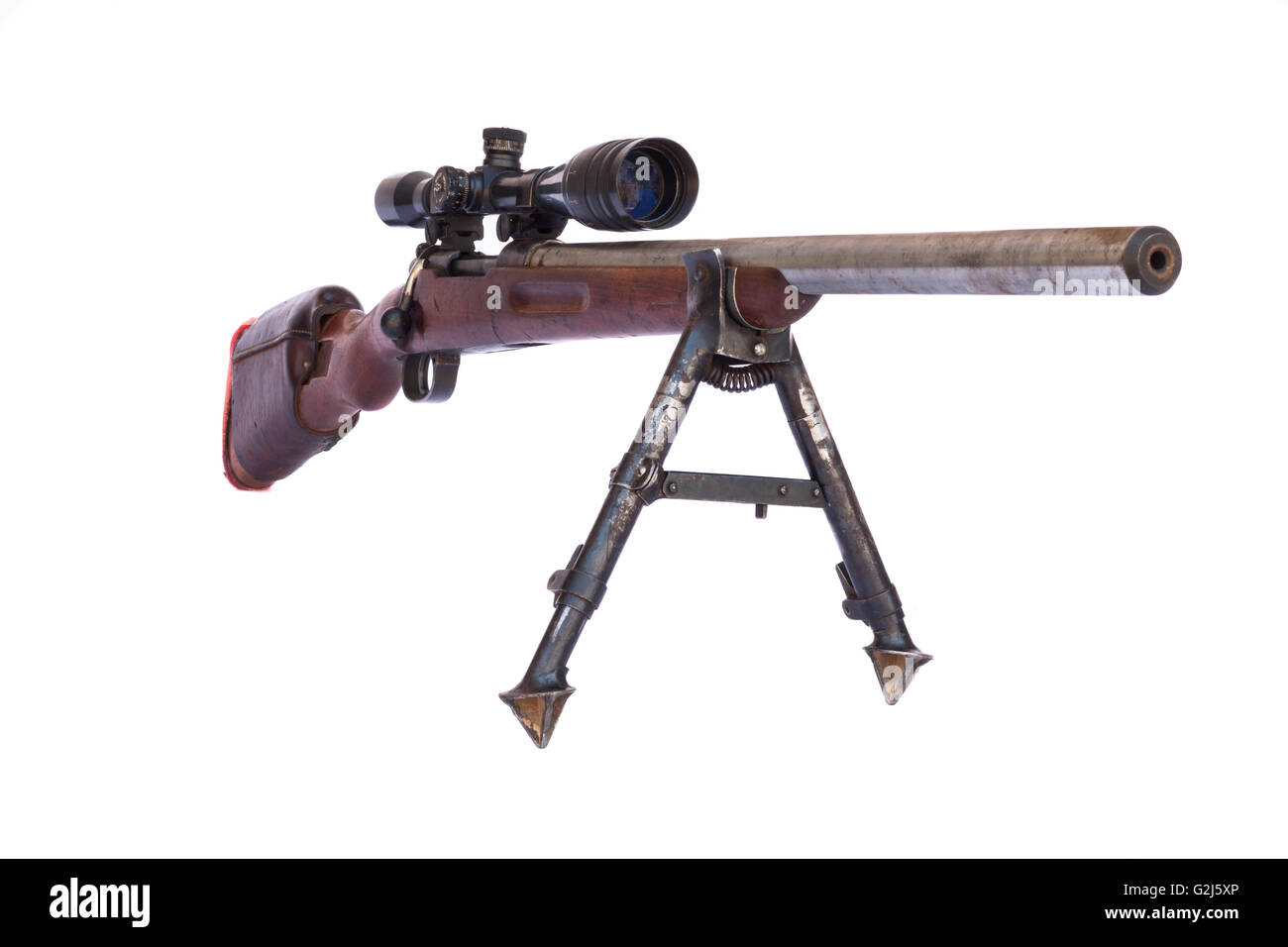 old sniper rifle with scope atached on a tripod isolated on white
