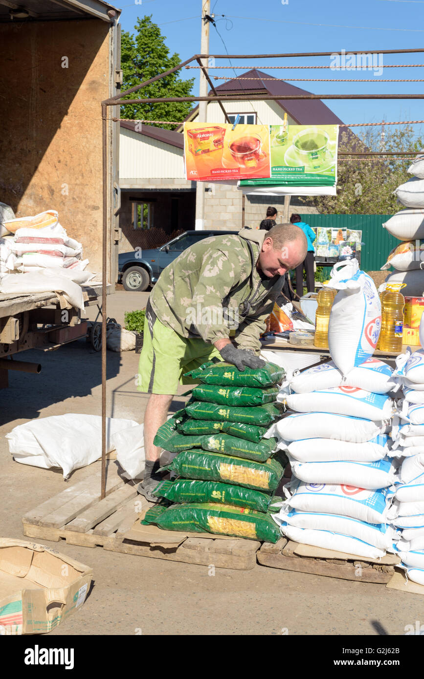 Russian flour seller moves sacks of flour on his market stall for sale to members of the public - Stock Image