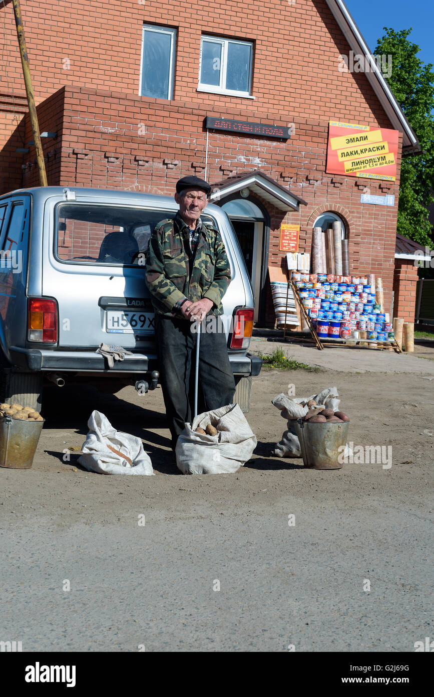 Elderly Russian man sells home produced crops and buckets of potatoes at a local farmers market to the public - Stock Image