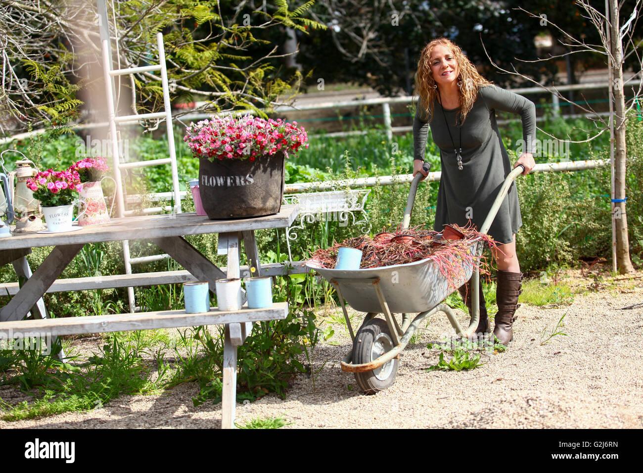 Woman works in her garden arranging flowers in a flowerpot Stock Photo