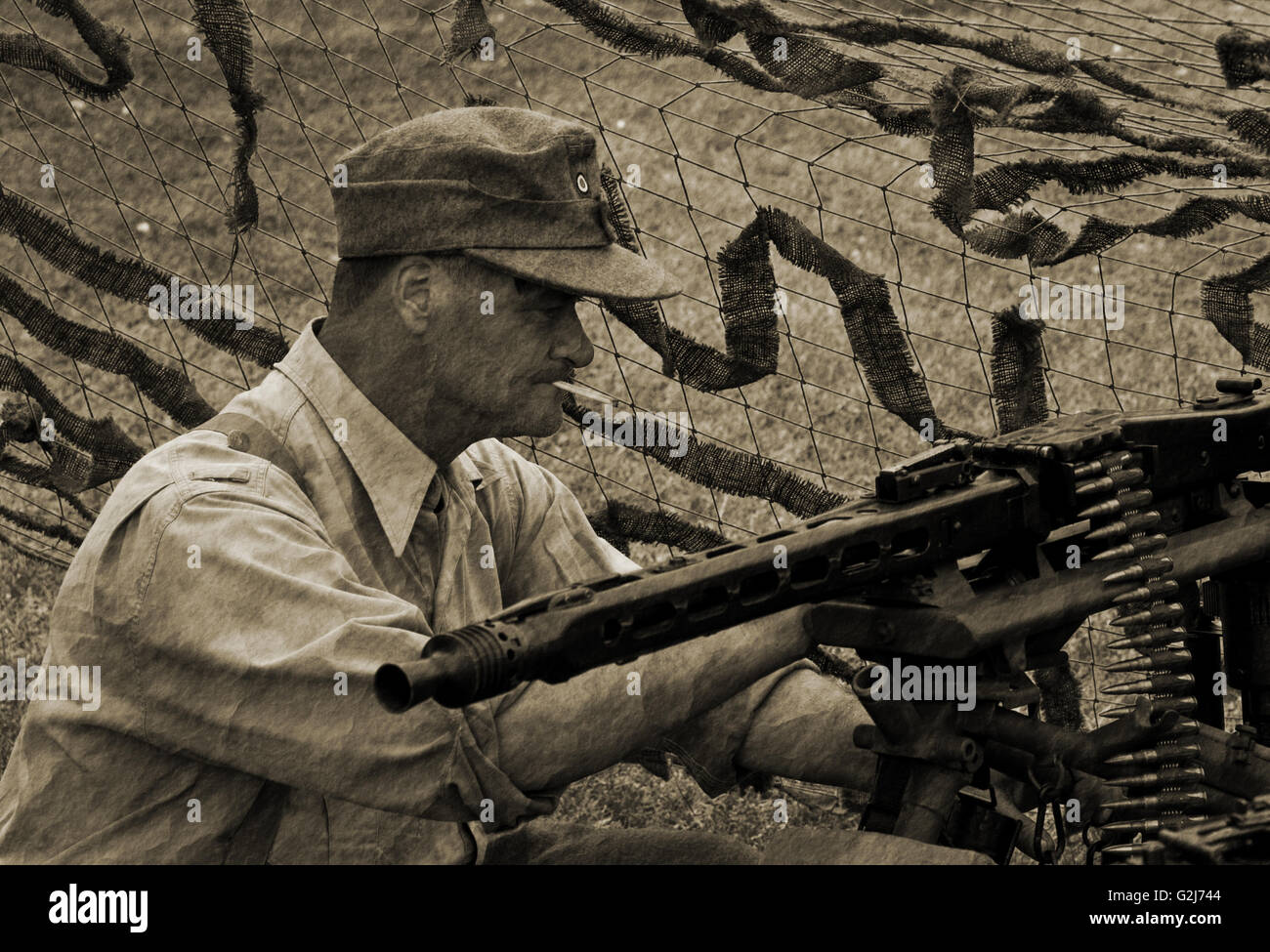 A Wehrmacht MG42 gunner takes time to service his weapon Stock Photo