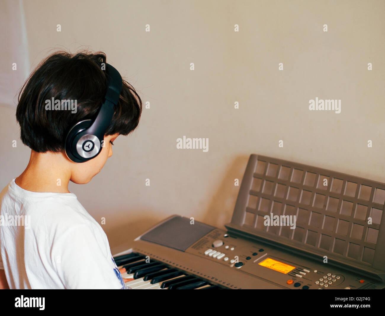 young boy of seven produces music on a Synthesizer keyboard - Stock Image