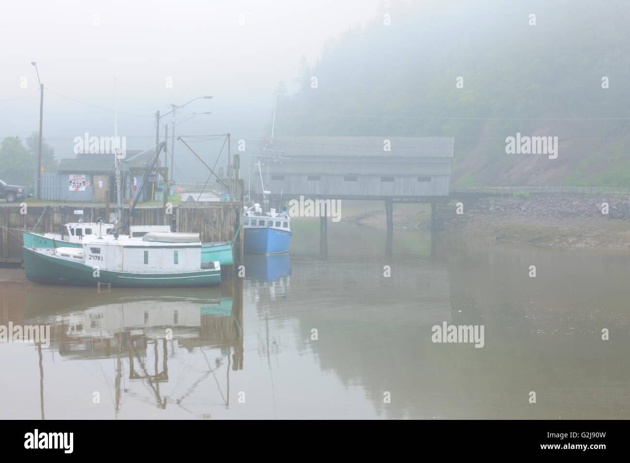 FIshing boats  in fog and Vaughn Creek # 1 Irish River Covered Bridge Saint Martins New Brunswick Canada - Stock Image