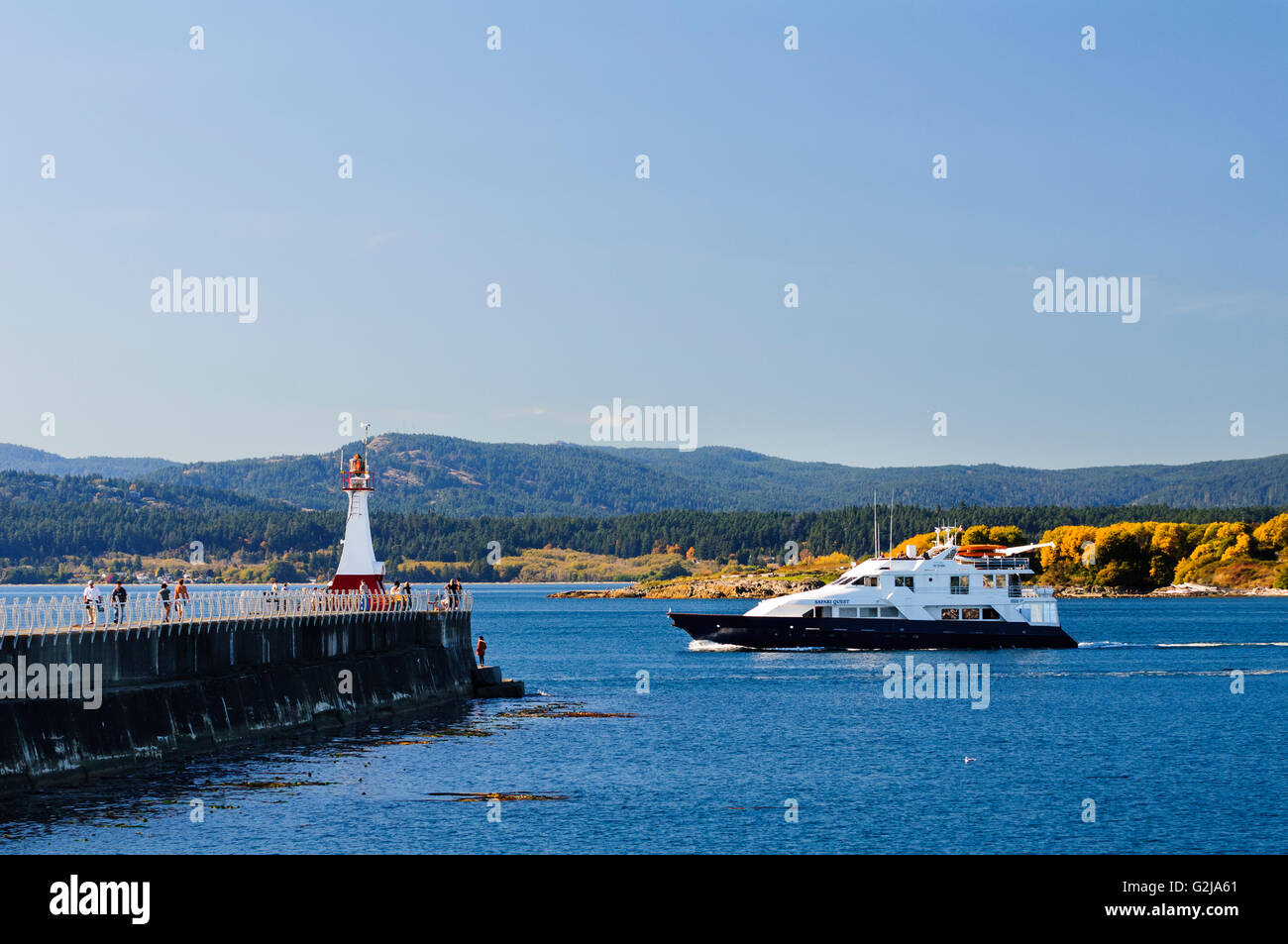 A private yacht, Safari Quest, heads past the Ogden Point Breakwater Lighthouse in Victoria, British Columbia. - Stock Image
