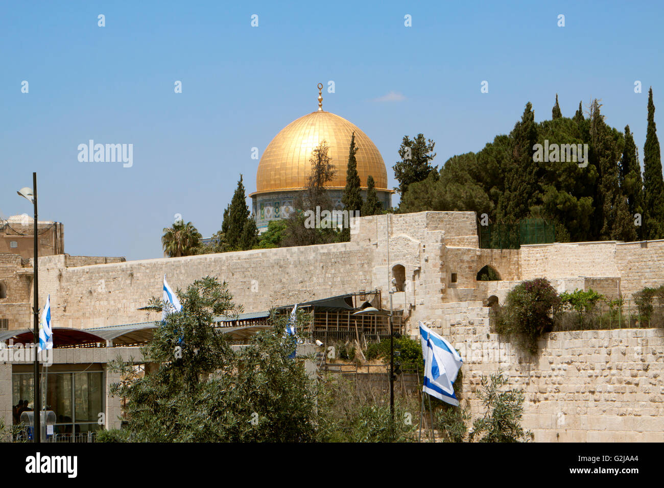 golden mosque on top of the wailing wall in jerusalem with israeli flags - Stock Image