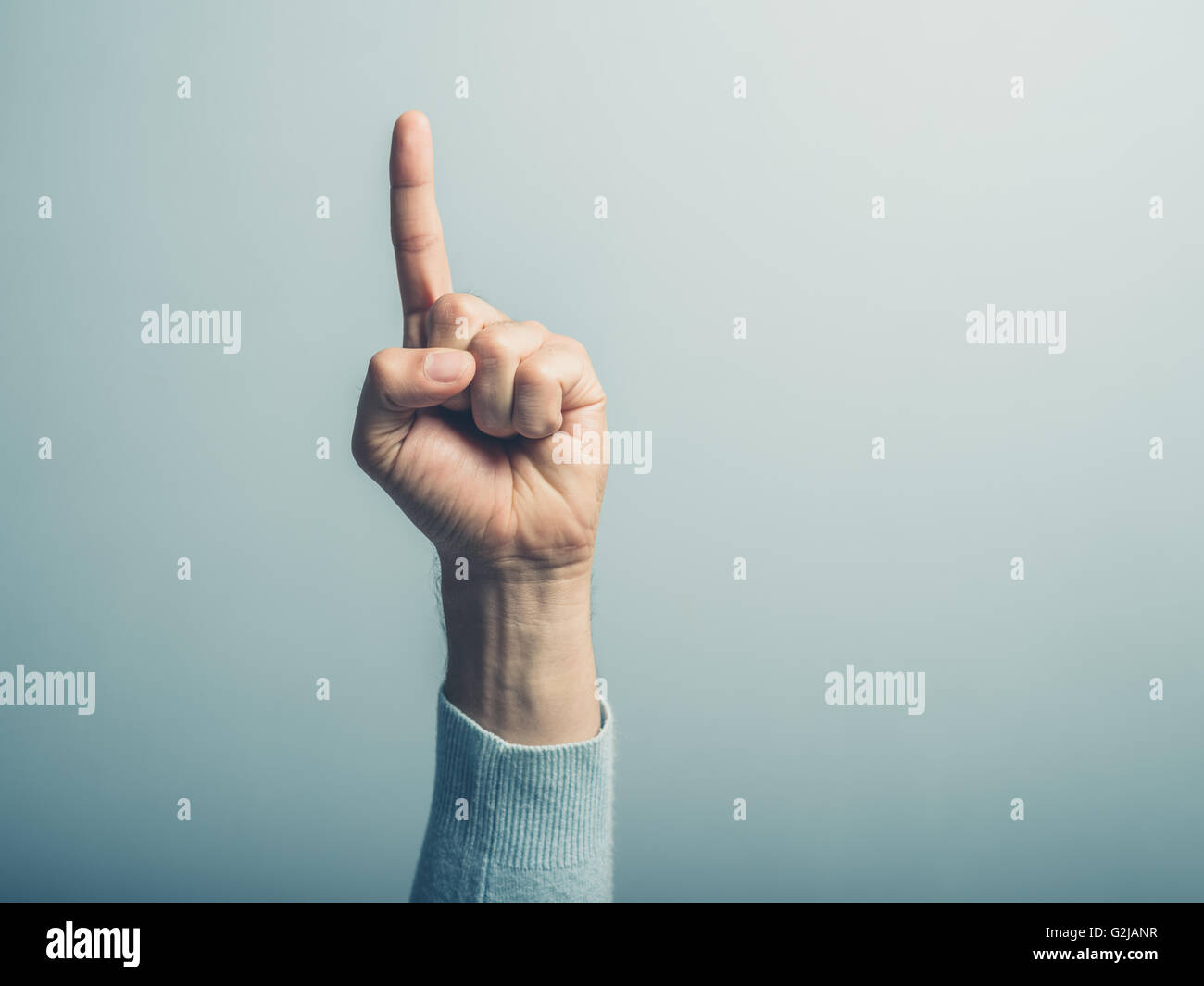 A male hand with the index finger pointing up - Stock Image