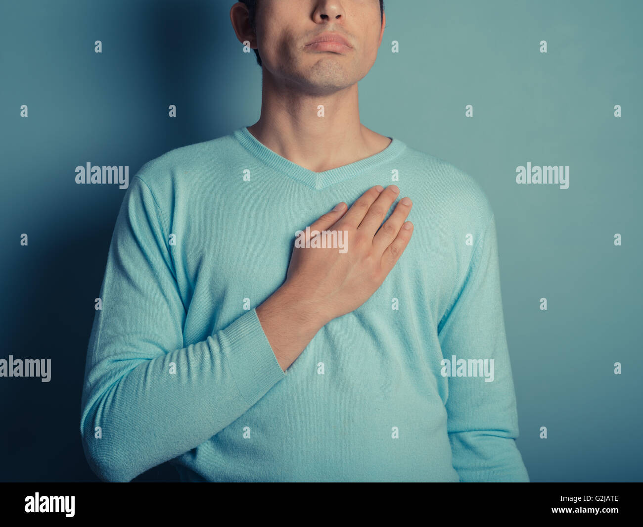 A young man wearing a blue jumper is placing his hand on his chest - Stock Image