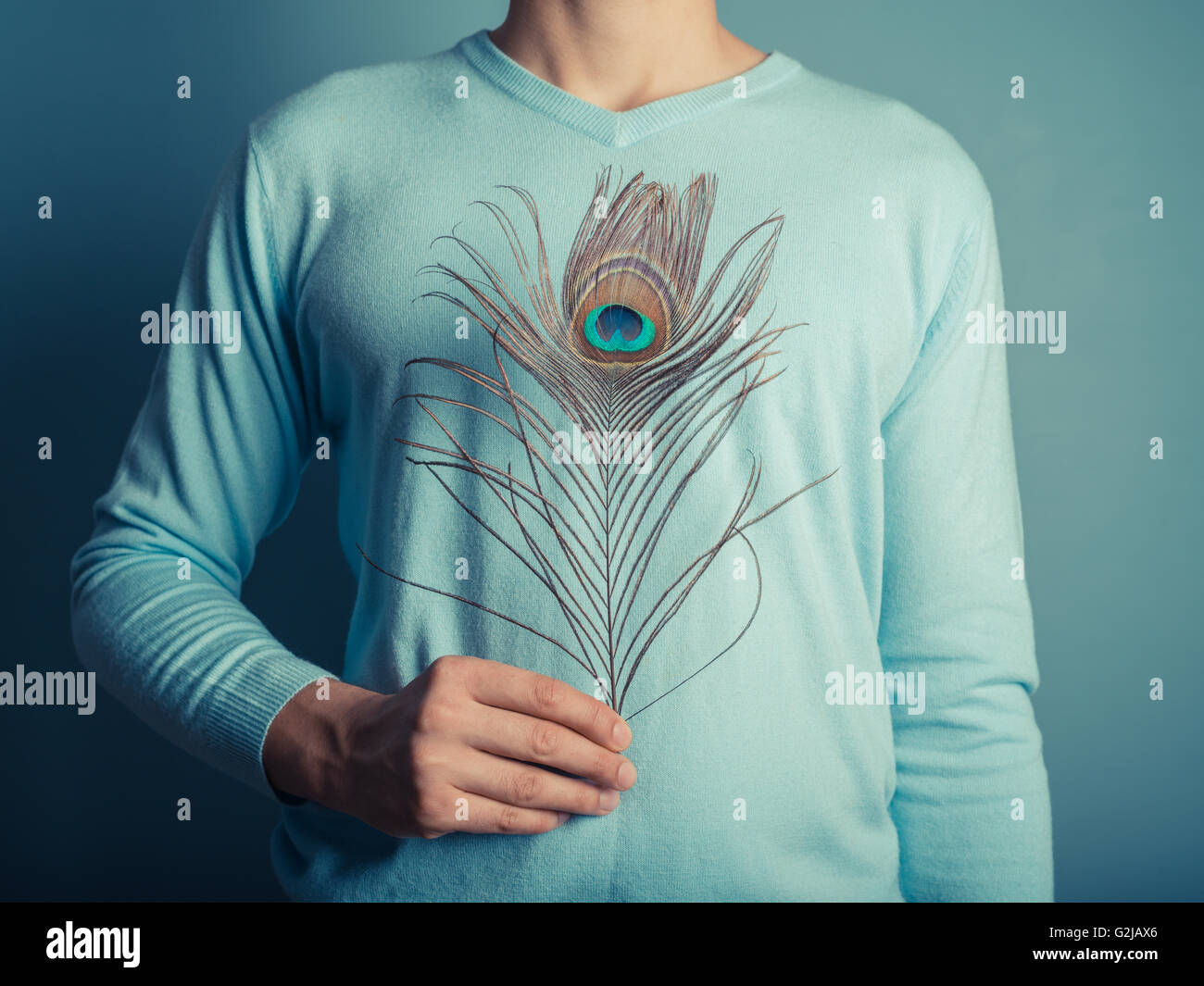 A young man is holding a pretty peacock feather - Stock Image