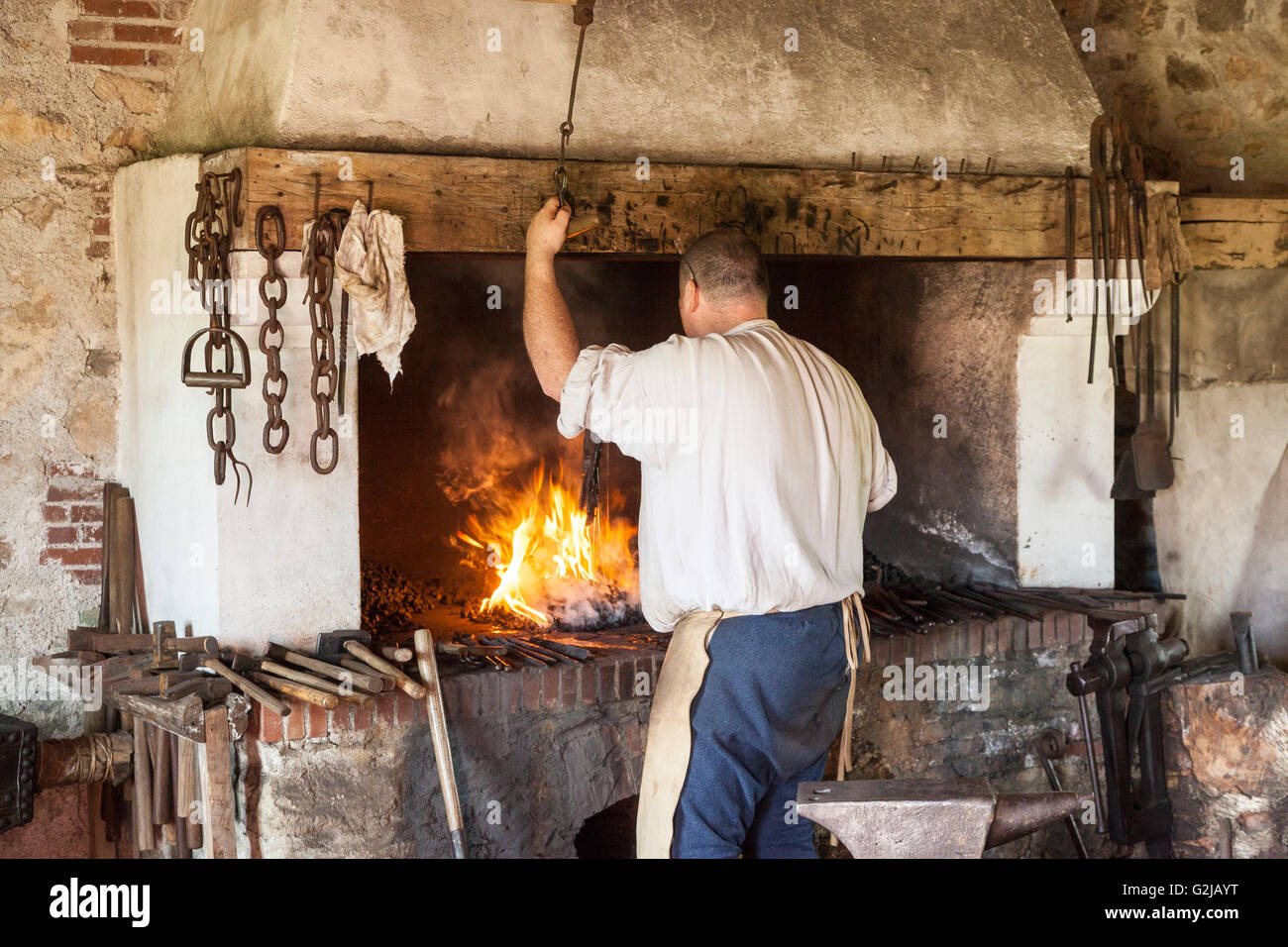 Man tending fire Artillery Forge Fortress Louisbourg National Historic Site in Louisbourg Nova Scotia - aritllery - Stock Image