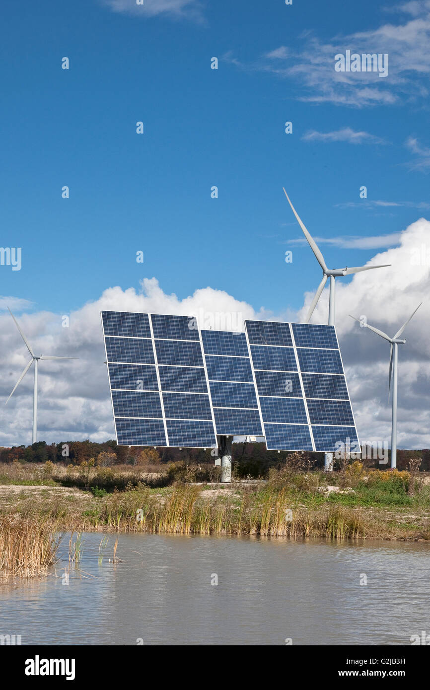 Solar panels on tracking system and windmills in farmland of southwestern Ontario (near Lake Erie), Ontario, Canada. - Stock Image