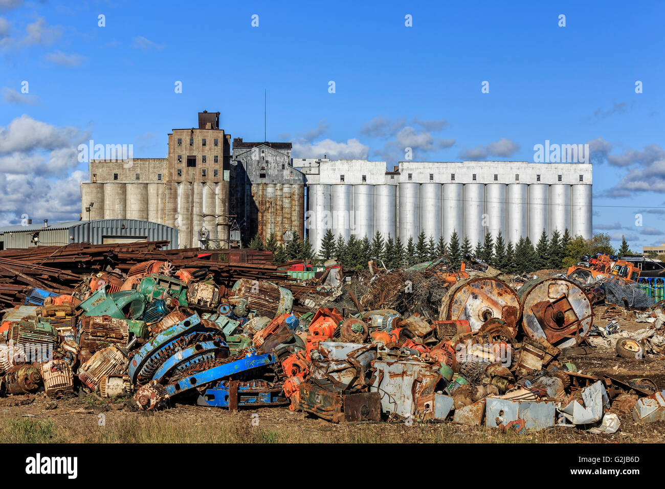 Scrap metal recycling, with an abandoned grain elevator in background, Thunder Bay, Ontario, Canada. - Stock Image