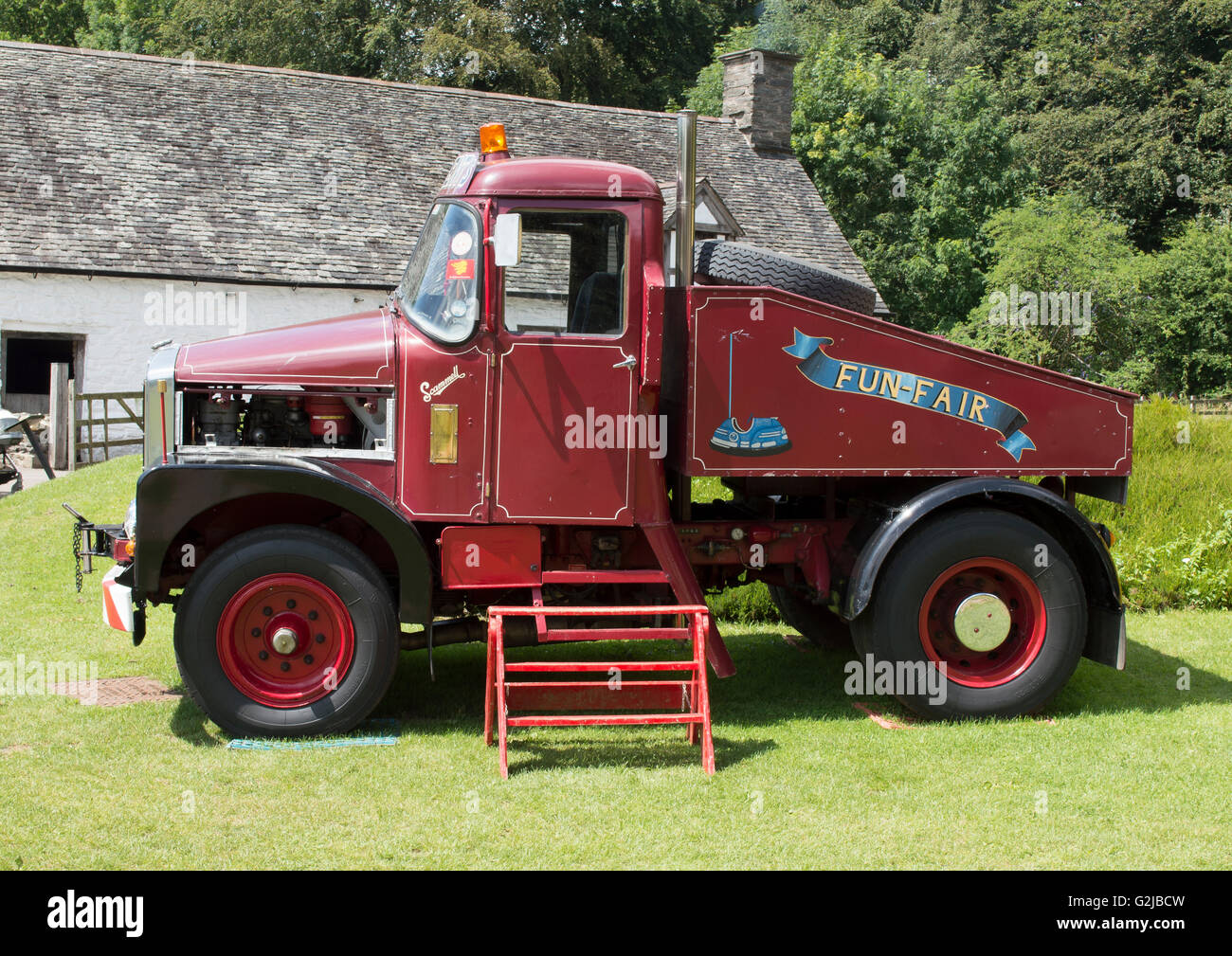 Side view of old red Scammell fun fair truck in sunshine at St Fagans South Wales - Stock Image