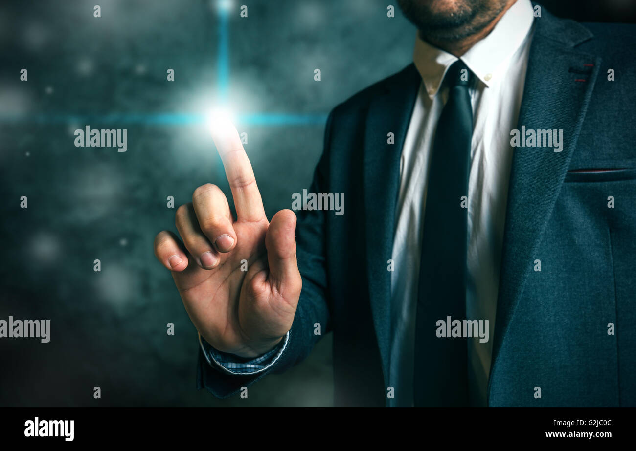 Businessman pushing virtual screen interface button, concept of modern futuristic technology in service of business - Stock Image
