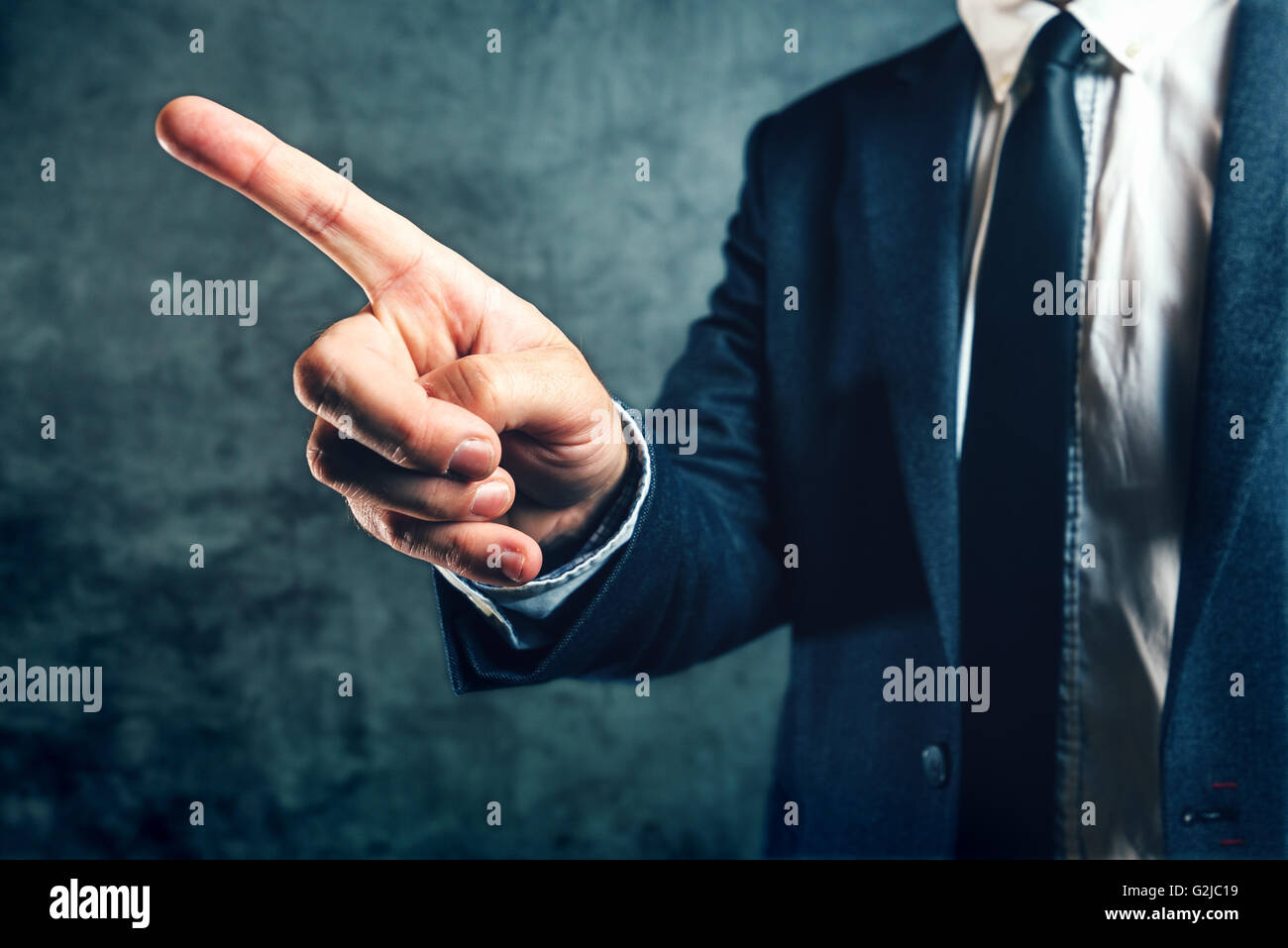 Getting fired from job, office manager showing way out with finger pointing to exit door. - Stock Image