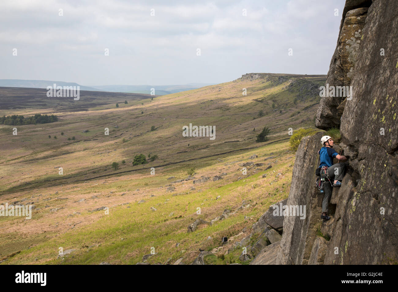 Climber on cliffs of Stanage Plantation in the Peak District, Derbyshire, England. - Stock Image