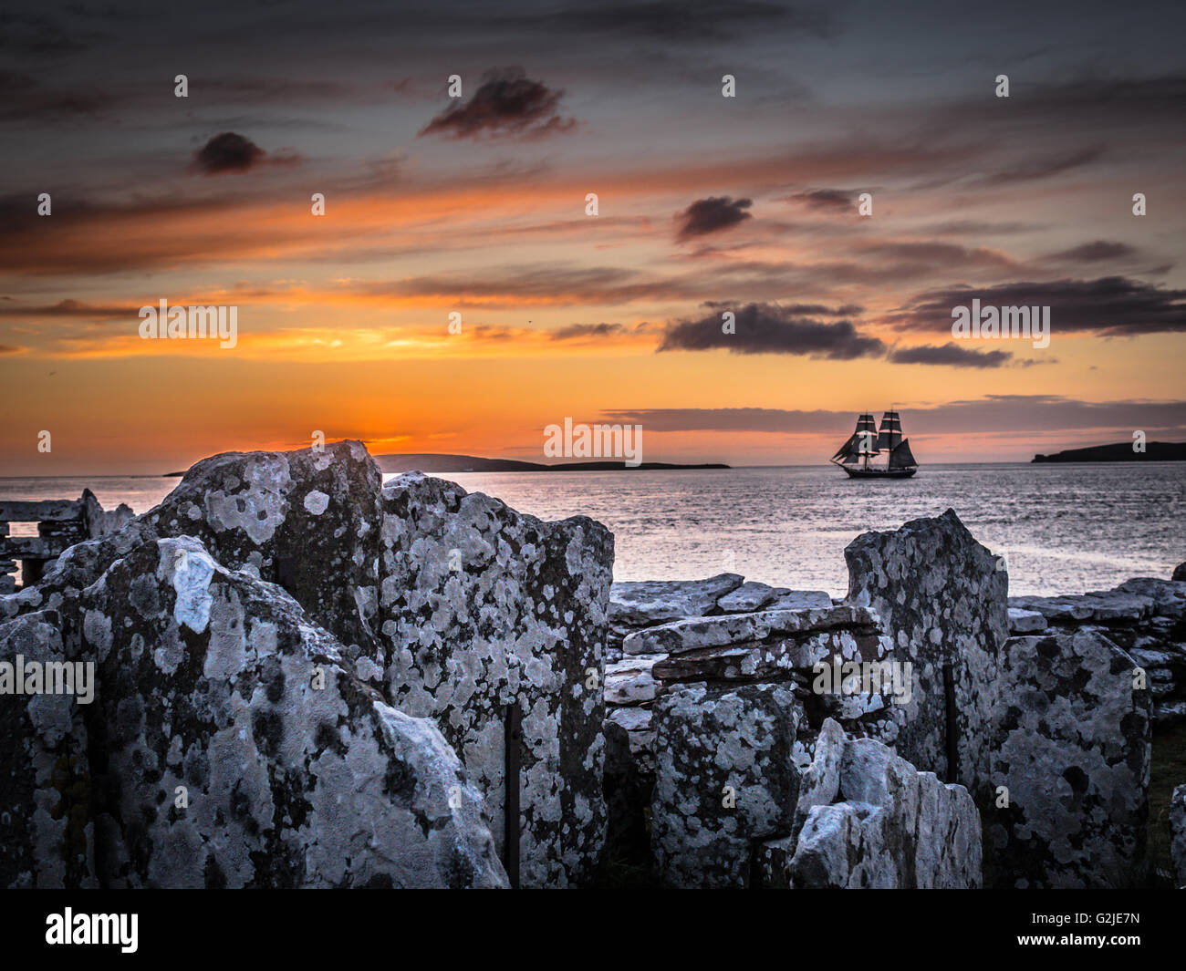 Square rigged tall ship Morgenster leaves Orkney at sunset between Eynhallow island and mainland, seen from the - Stock Image