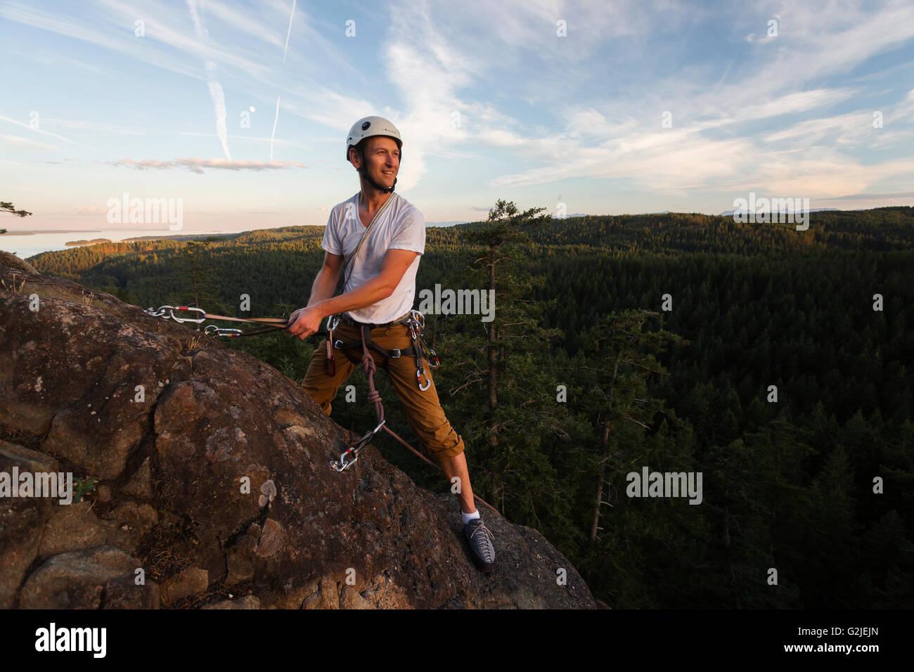A male climber on Sunset Slab sets up a belay station while climbing on Quadra Island Quadra Island Northern Gulf - Stock Image
