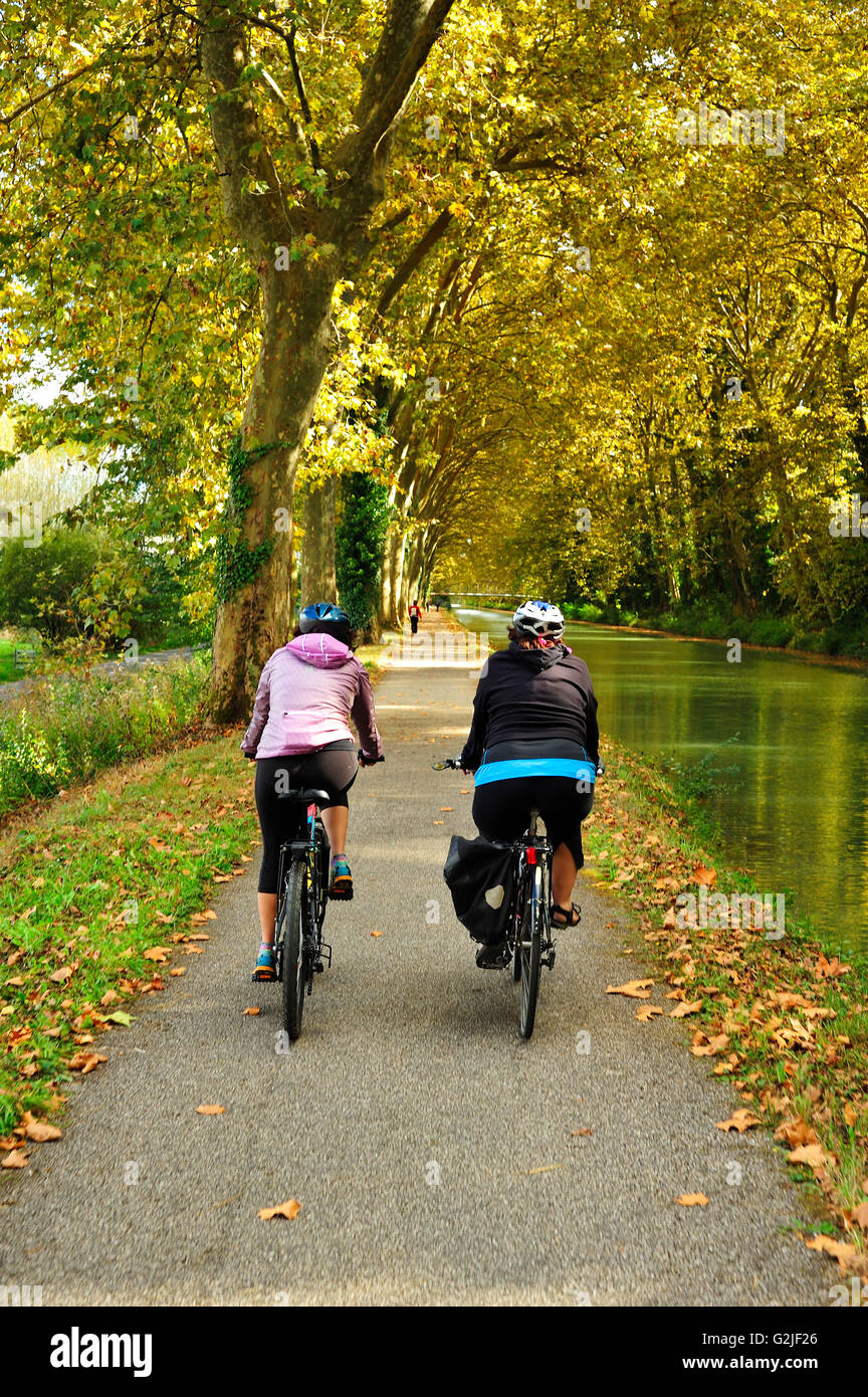 two cyclists on towpath beside the Canal de Garonne near Marmande, Lot-et-Garonne Department, Aquitaine, France - Stock Image