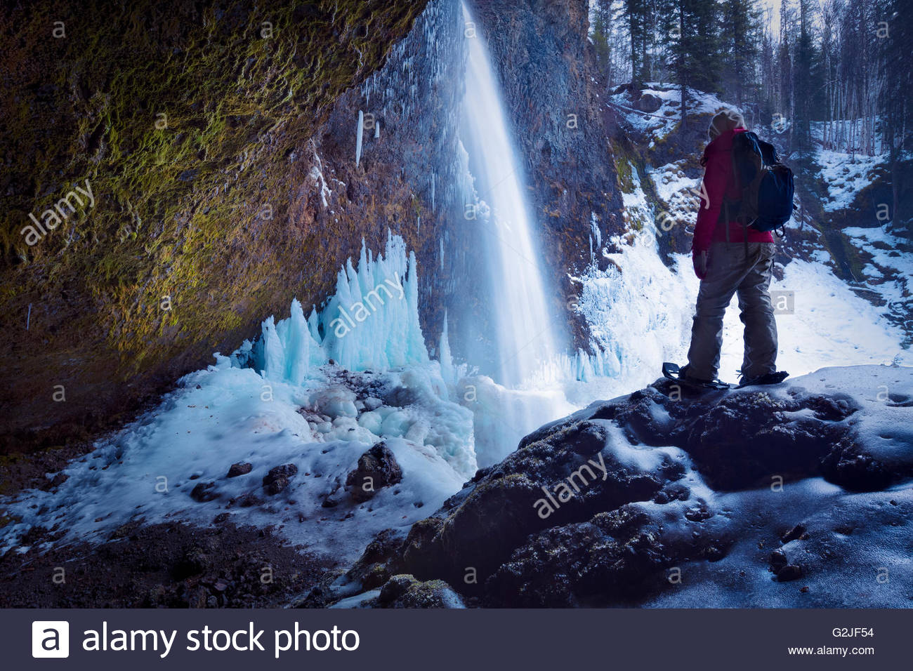 Snowshoer by watefall in winter, Wells gray provincial park, British Columbia, Canada - Stock Image