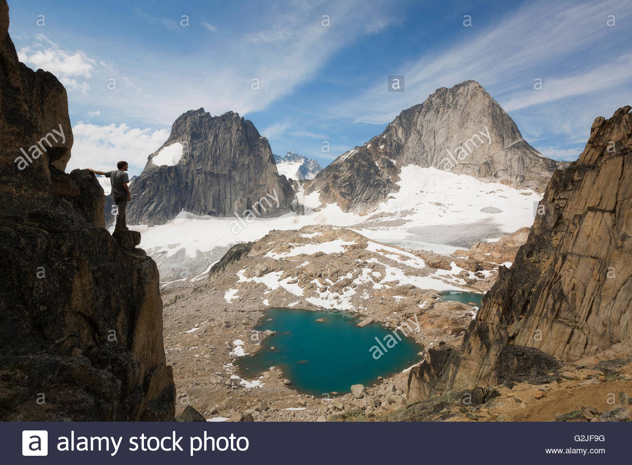 Male hiker scrambling on Eastpost Spire in the Purcell Mountain range, Bugaboo Provincial Park, British Columbia, - Stock Image