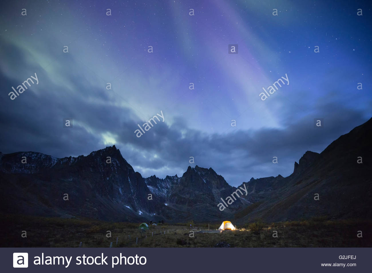 The aurora borealis above Grizzly Lake campground and an illuminated tent, Tombstone Territorial Park, Yukon Territory, Stock Photo