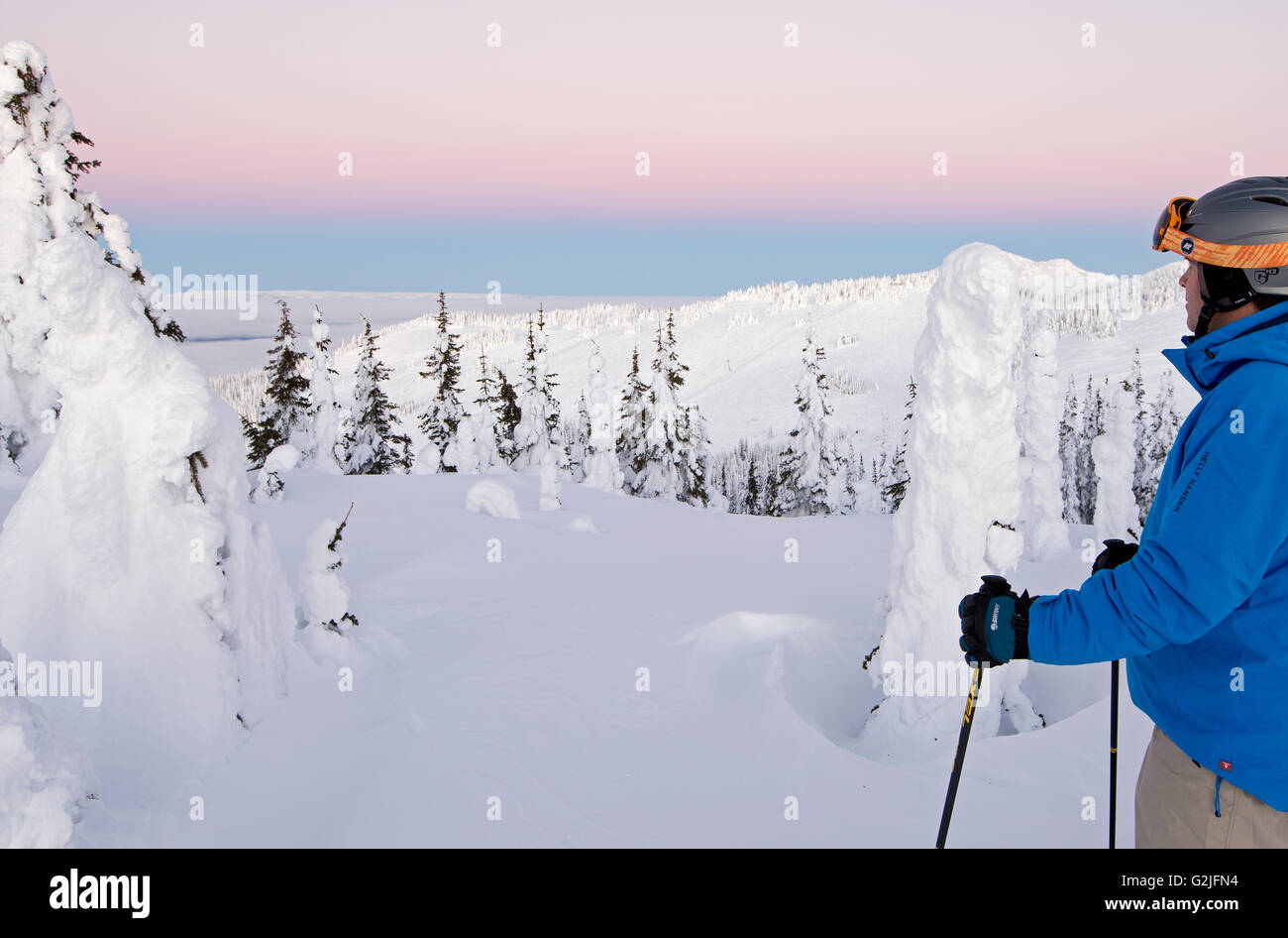 A skier among snow ghosts surveys beautiful landscape before sunrise top Sun Peaks Resort Thompson Okangan region - Stock Image