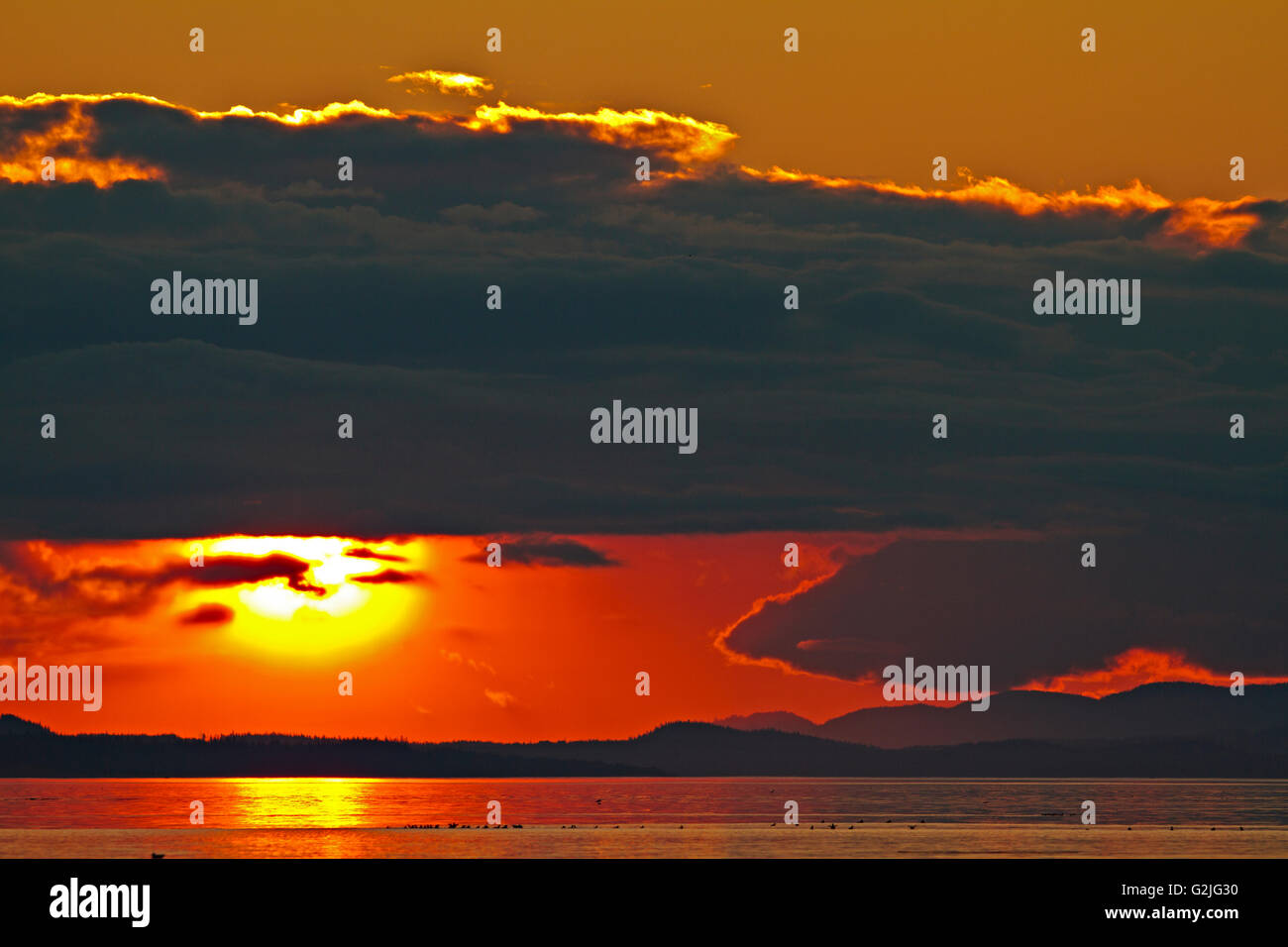 Sunset with cloud cover over Cormorant Island and vancouver Island North, British Columbia, Canada. - Stock Image