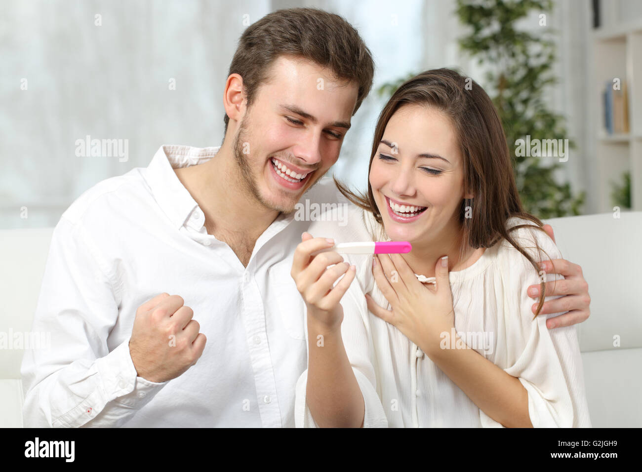 Happy excited couple making positive pregnancy test and celebrating - Stock Image