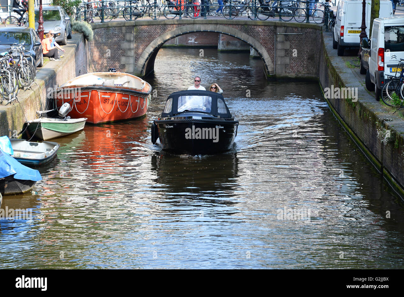 couple navigate boat on canal under bridge in central Amsterdam city. - Stock Image