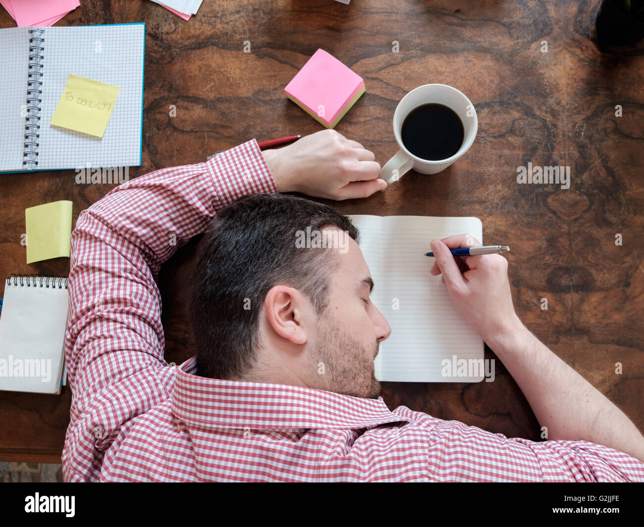 portrait of exhausted worker sleeping on his desktop - Stock Image