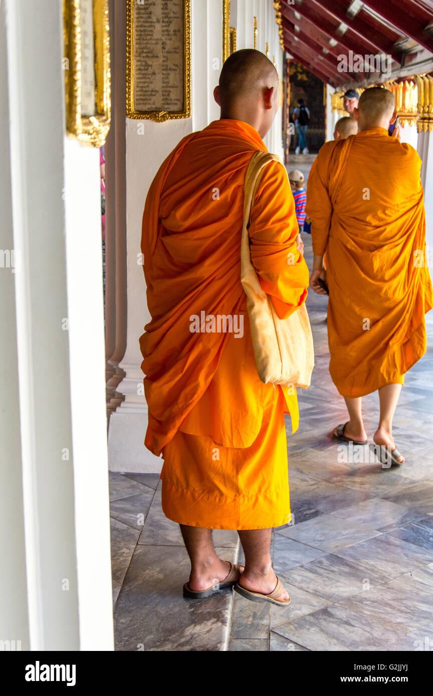 Rear View of Bhuddist Monks on Orange Robes Walking - Stock Image