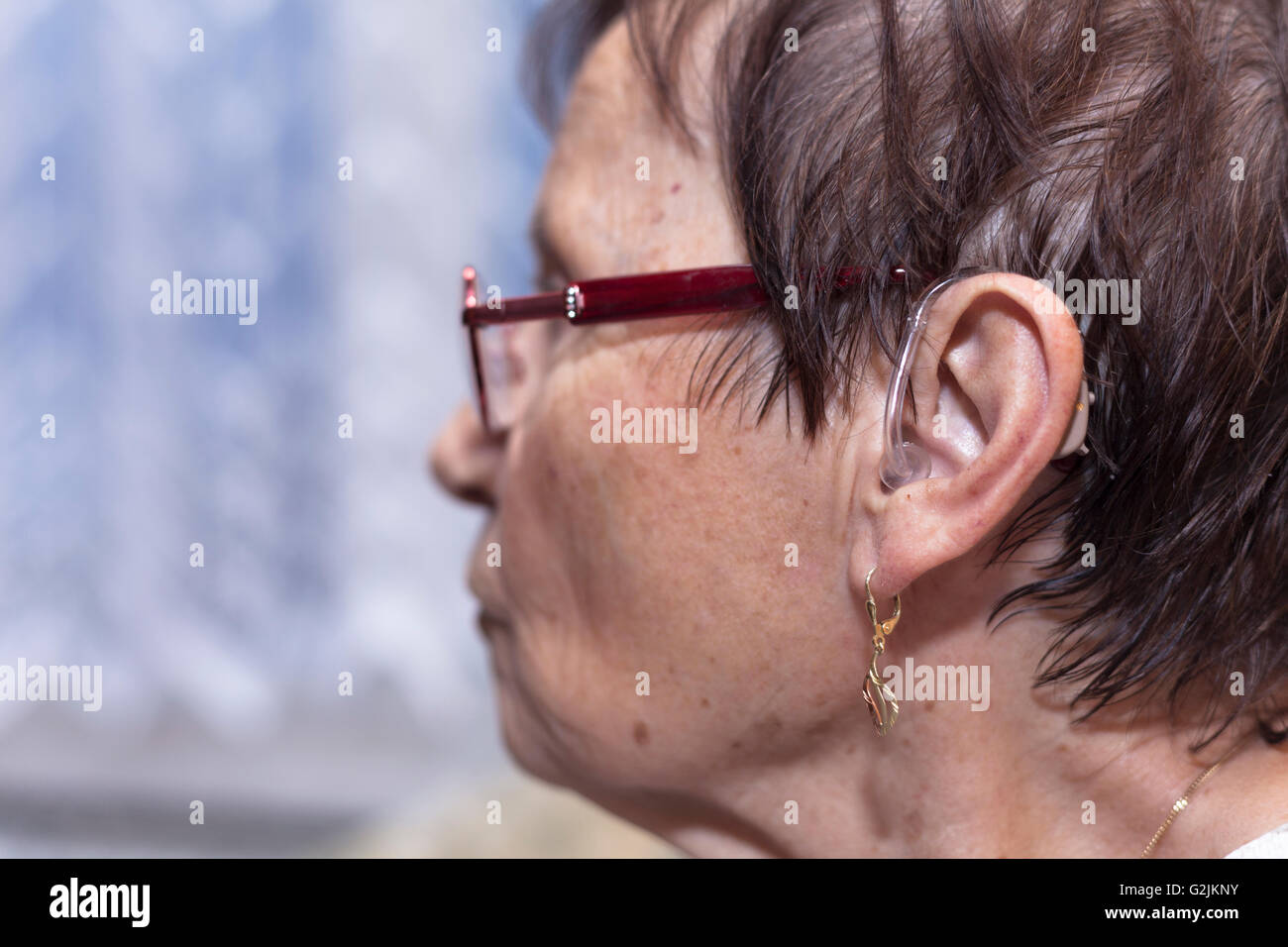 Profile of a senior woman with hearing aid. - Stock Image