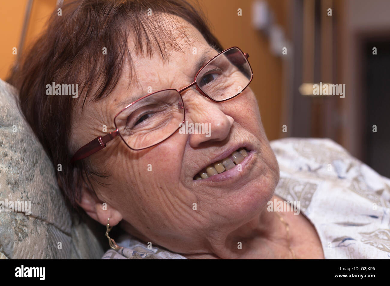 Closeup of a senior woman grimacing and frowning. - Stock Image