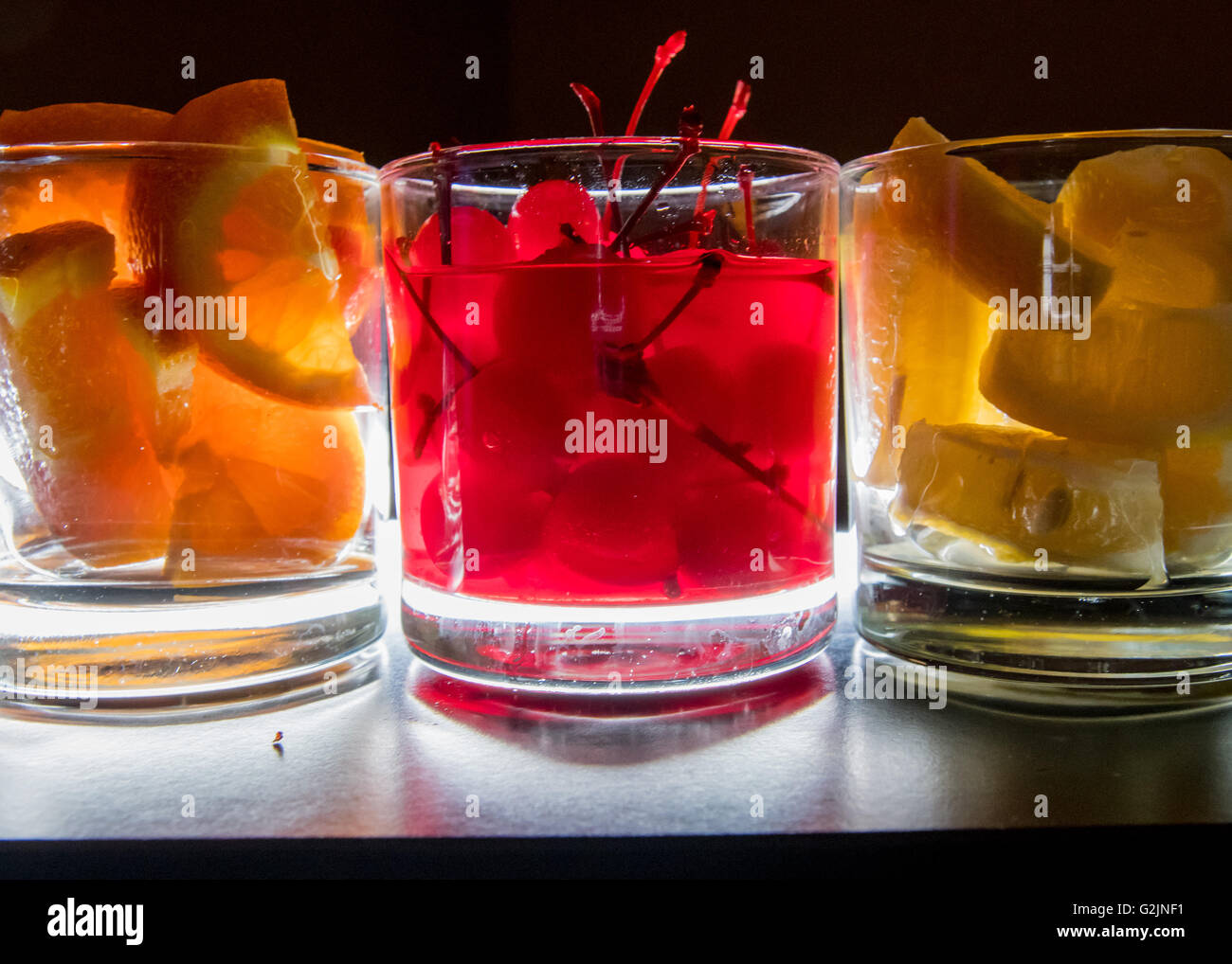 Oranges Cherries and Lemons Backlit provide mixers for an open bar - Stock Image