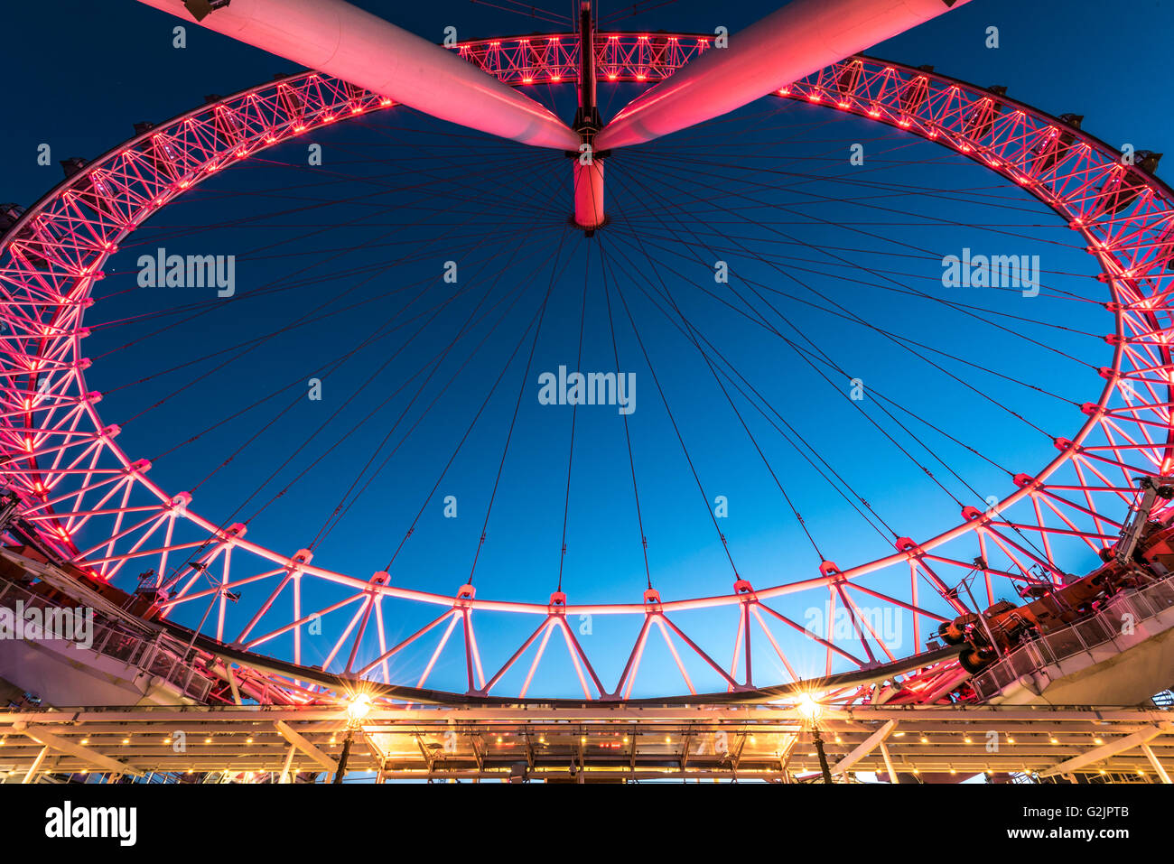 London Eye illuminated in the colour red by its current sponsor Coca Cola - Stock Image