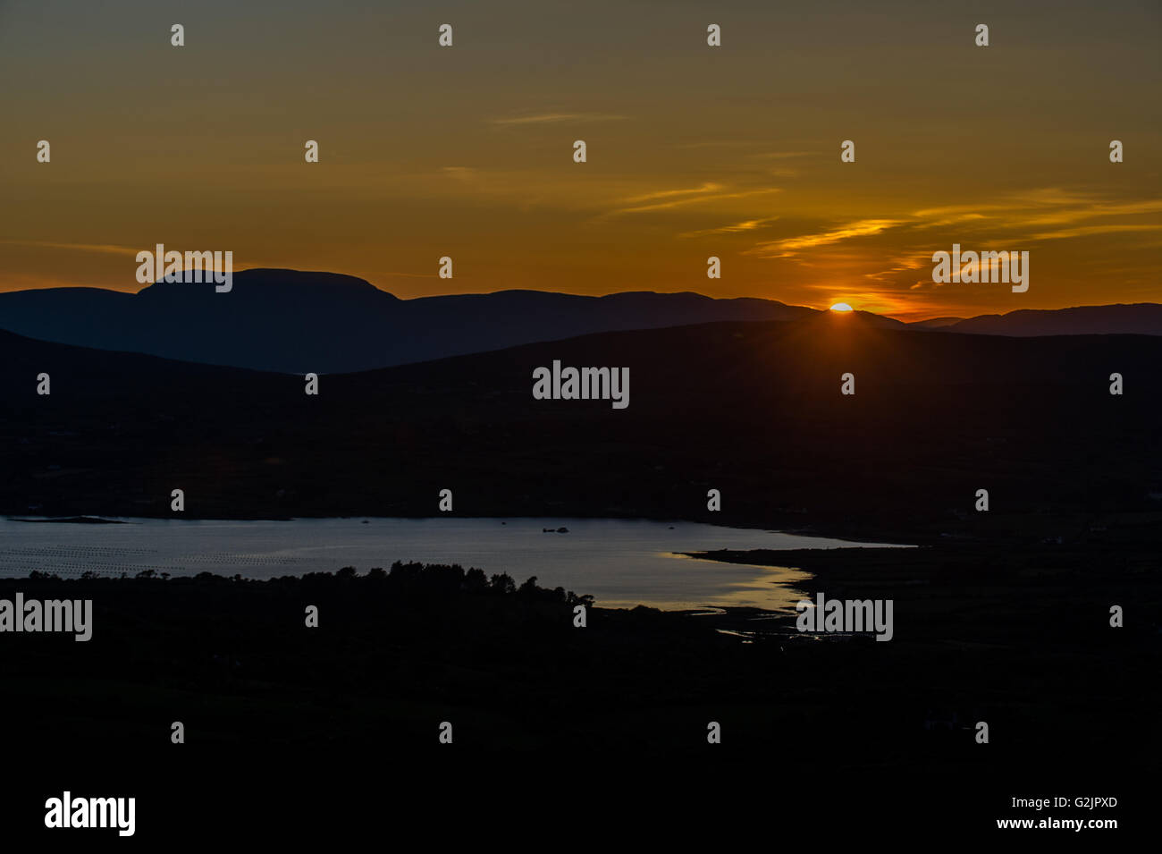 A sunset pictured from Mount Corrin, Ballydehob, on the Sheep's Head Way overlooking  Blairs Cove, West Cork, - Stock Image