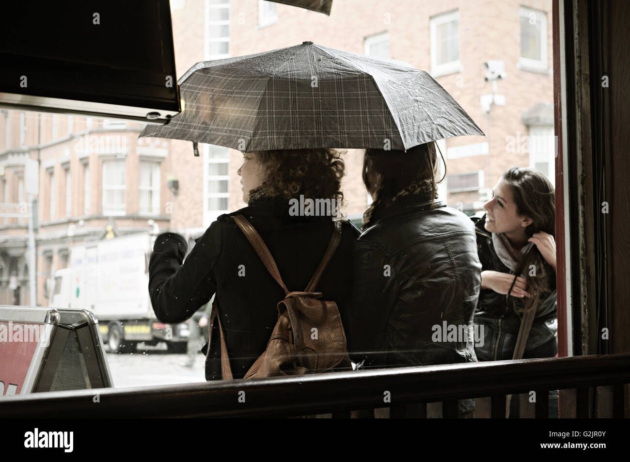 Young women with an umbrella during a shower seen from inside a restaurant in Dublin, Temple Bar quarter, Ireland Stock Photo