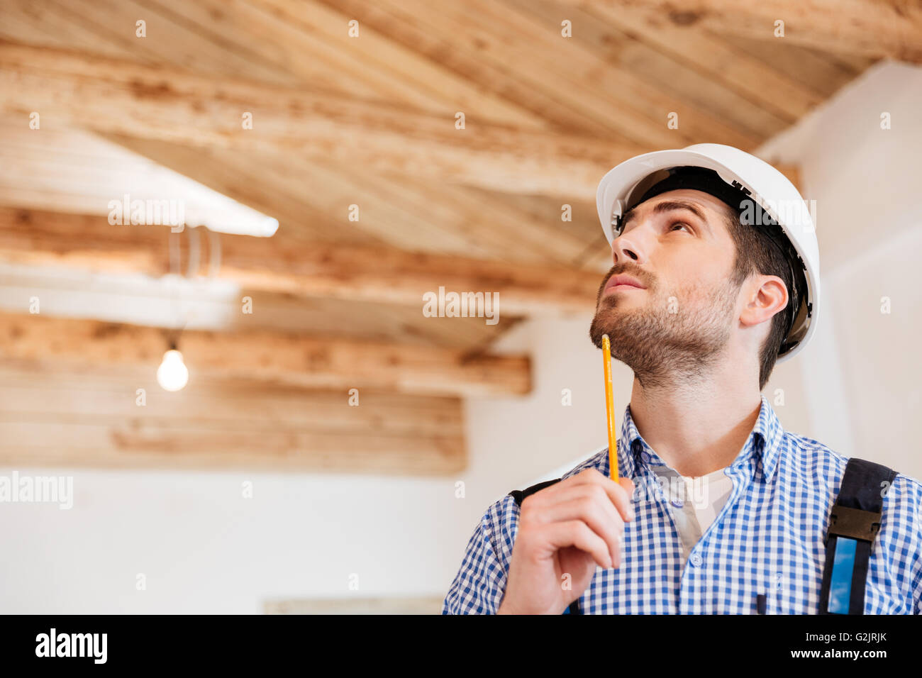 Close-up portrait of a pensive builder that examines his working place - Stock Image